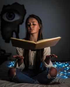 woman reading a book sitting on mattress near the blue string light inside the room