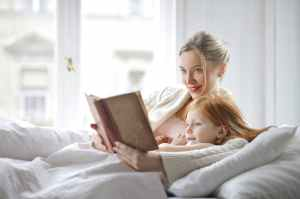 woman and a girl on bed holding a book