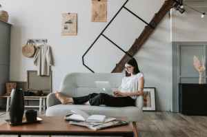 content young woman using laptop in modern living room